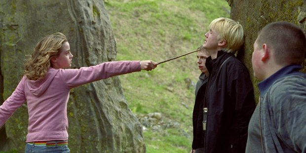 Emma Watson as Hermione Granger, points her wand at Tom Felton, who plays Draco Malfoy.