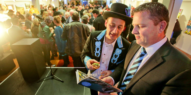 Festival director Pitsch Leiser, (left), reveals the 2016 Harcourts Hawke's Bay Arts Festival programme to sponsor Harcourts managing director Kaine Wilson. Photo / Warren Buckland