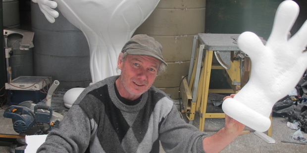Auckland sculptor Mike Walsh at work in Ohakune with a brussel sprout behind him. The hand is for a parsnip.
