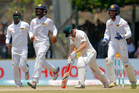 Australia's Adam Voges reacts after being bowled out as Sri Lanka's Dinesh Chandimal, right, and Angelo Mathews, left, and Kusal Mendis celebrate. Photo / AP