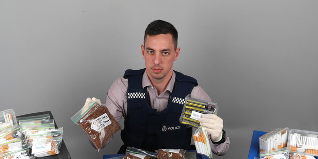 Wellington Police Constable Harley Jay Mounsey with the haul of tobacco seized as part of investigations into thefts from Imperial Tobacco. Photo / Supplied