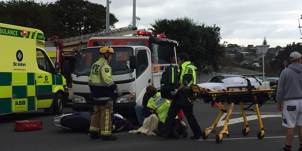 A scooter rider is treated by ambulance staff after being in a collision with a light truck. Photo/George Novak