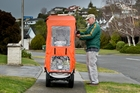 Taradale resident John Kerr adjusts the wet weather cover on his mobility scooter as the rain comes down. Photo / Warren Buckland