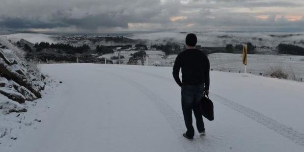 Loading A man walks to work in Dunedin after ditching his car this morning. Photo / Stephen Jaquiery