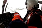Lowe rescue helicopter crewmen make a tricky landing at the snowbound Sunrise Hut in the Ruahine Ranges to rescue a woman with a broken shoulder