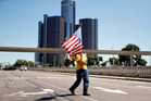 A woman at a protest as Republican presidential candidate Donald Trump delivered an economic policy speech in Detroit. Photo / AP