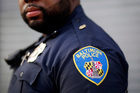 Baltimore Police Department Officer Jordan Distance stands on a street corner during a foot patrol in Baltimore. Photo / AP
