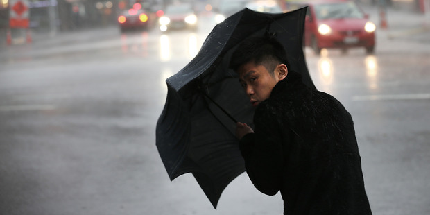 People brave the bad weather in Auckland CBD. Photo / Doug Sherring