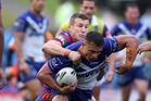 Sam Perrett of the Bulldogs is tackled by Trent Hodkinson of the Knights during Canterbury's win over Newcastle yesterday. Photo / Getty Images