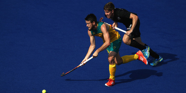 Matt Gohdes of Australia runs past Black Stick James Coughlan during their Olympic clash earlier today. Photo / Getty Images