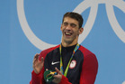 Michael Phelps with his Gold medal from the Men's 200m Butterfly. Photo / Getty Images