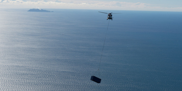 On route - A RNZAF NH90 moves a shipping container to White Island. Photo/supplied