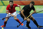 Black Sticks Nick Woods competes for the ball in the teams round robin match against Great Britain. Photo / AP