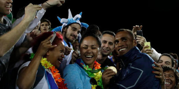 Fiji's Osea Kolinisau, right, poses with supporters after winning the men's rugby sevens gold medal match. Photo / AP