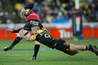 Hurricanes halfback TJ Perenara makes a tackle on Lions wing Ruan Combrinck during the 2016 Investec Super Rugby final at Westpac Stadium in Wellington. Photo / Mark Mitchell