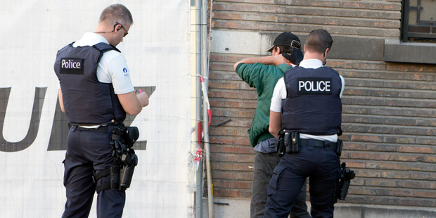 Police officers check the identification of a man near the police headquarters in Charleroi. Photo / AP