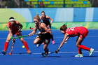 New Zealand's Anita McClaren, center, fights for the ball with South Korea's Hyungi Kim. Photo / AP