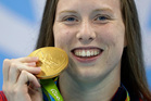 United States' Lilly King shows off her gold medal during the ceremony for the women's 100-meter breaststroke final. Photo / AP.