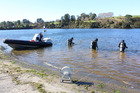 Police National Dive Squad divers enter Lake Arapuni from Arapuni Landing as part of a grid search of waterways around the missing woman's home.