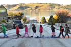 Ravensbourne School pupils use towels to cross Wanaka St outside their school, during frosty weather yesterday. Photo / Otago Daily Times