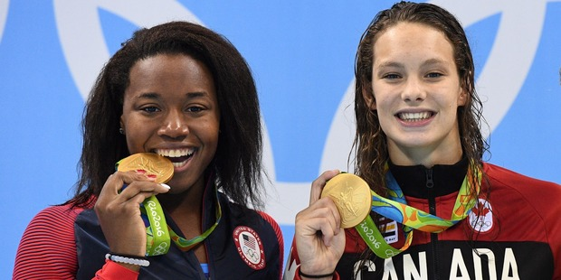Canada's Penny Oleksiak, right, and United States' Simone Manuel celebrate their tie for gold in the women's 100-meter freestyle. Photo / AP