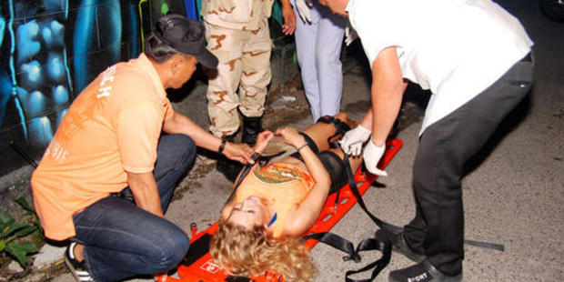 Rescue workers help an unidentified woman after a bomb blast in the southern resort city of Hua Hin. Photo / AP