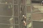 A man is trying to scale the all-glass face of Trump Tower in New York City using suction cups.