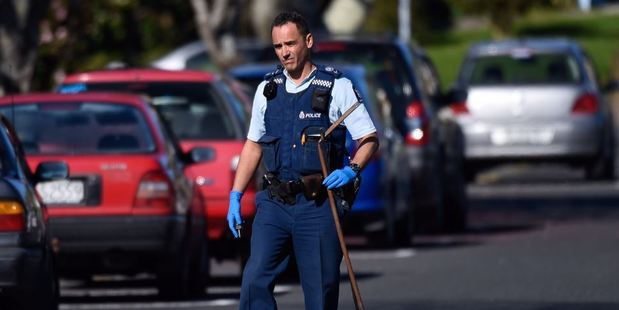 A police officer removes what appears to be a homemade spear gun from a property in Brookfield today. Photo/George Novak