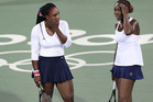 Venus Williams, of the United States, right, talks with her sister Serena after losing a point in a doubles match against Lucie Sarfarova and Barbora Strycova. Photo / AP