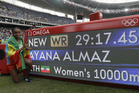 Ethiopia's Almaz Ayana poses next to a scoreboard showing her new world record in the women's 10,000-metre final. Photo / AP