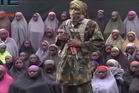 This undated image taken from video distributed today shows an alleged Boko Haram soldier standing in front of a group of girls alleged to be some of the 276 abducted Chibok girls. Photo / AP