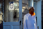 A member of the Al-Furqan Jame Masjid mosque stands near a police sketch of a suspect believed to have shot the mosque's imam. Photo / AP