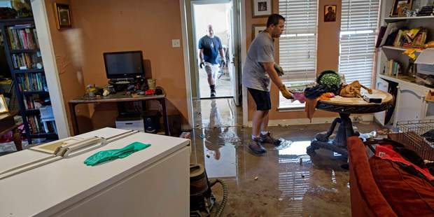 Raymond Lieteau pulls furniture today out of his flood damaged home with the help of his friend Danny Lemoine, 48, in Baton Rouge. Photo / AP