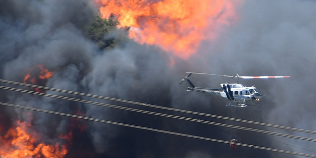 A helicopter flies near flames from the Bluecut Fire in San Bernardino, California. Photo / AP