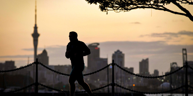 A jogger on Tamaki Drive takes advantage of a clear winter evening as the sun sets over the Auckland CBD and Skytower. Photo: Jason Oxenham