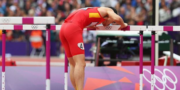 Xiang Liu of China kisses a hurdle after getting injured in the Men's 110m Hurdles Round 1 Heats at the London 2012 Olympic Games. Photo / Getty