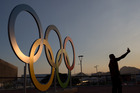 A man takes a selfie in front of the Olympic rings in Olympic Park. Photo / Getty