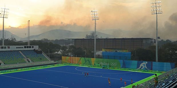 A bushfire burns roughly 10 miles from the Olympic field hockey venue during the 2016 Summer Olympics in Rio de Janeiro. Photo / Getty Images