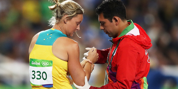 Loading Kim Mickle of Australia is assisted by medical staff after being injured during the javelin. Photo / Getty