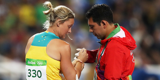 Kim Mickle of Australia is assisted by medical staff after being injured during the Women's Javelin Throw Qualifying Round during Rio Olympics. Photo / Getty Images