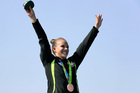 Lisa Carrington celebrates her bronze medal on the podium after the final of the women's K1 500m event. Photo / AP