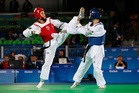 Iris Sing from Brazil, left, has defeated New Zealand's Andrea Kilday in the opening round of the women's 49kg taekwondo event. Photo / AP