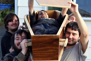 Jesse Hosie, Curtis Curry (front), Jeano Hosie (in coffin), Vaughn Holt and Jefferson Cameron-Kemp (rear) with the homemade coffin they are trying to sell on Facebook.