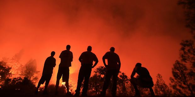 Residents watch as a wildfire burns near their homes off Morgan Valley Road in Lower Lake, Calif. Photo / AP