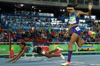 Bahamas' Shaunae Miller falls over the finish line to win gold ahead of United States' Allyson Felix, right, in the women's 400-meter final. Photo / AP.