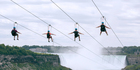 Tourists suspended above the water from zip lines make their way toward the mist of the Horseshoe Falls, on the Ontario side of Niagara Falls. Photo / AP