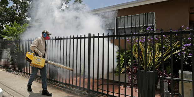A Miami-Dade County mosquito control worker sprays around a home in the Wynwood area of Miami. Photo / AP