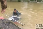 With seconds to spare, a woman is pulled from her car which had become stuck in rising floodwaters.