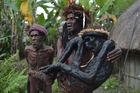 Chief Eli Mabel of the Dani tribe carries the mummified remains of his ancestor, Agat Mamete Mabel, in the village of Wogi in Wamena, Indonesia. Photo / AP
