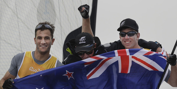 Loading New Zealand's Blair Tuke, left, and Peter Burling, right, celebrate with their coach Hamish Willcox after securing the 49er men gold medal. Photo / AP